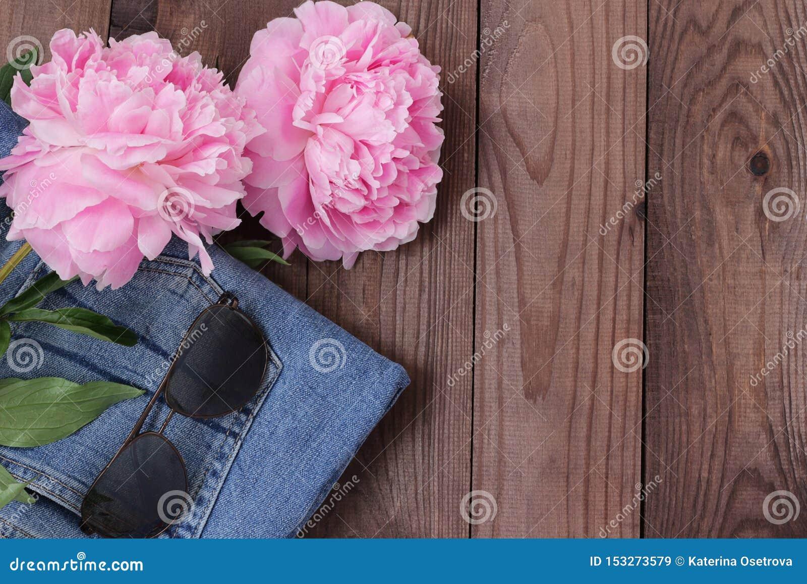 Denimuitrusting met flatlay zonglazen en bloemen