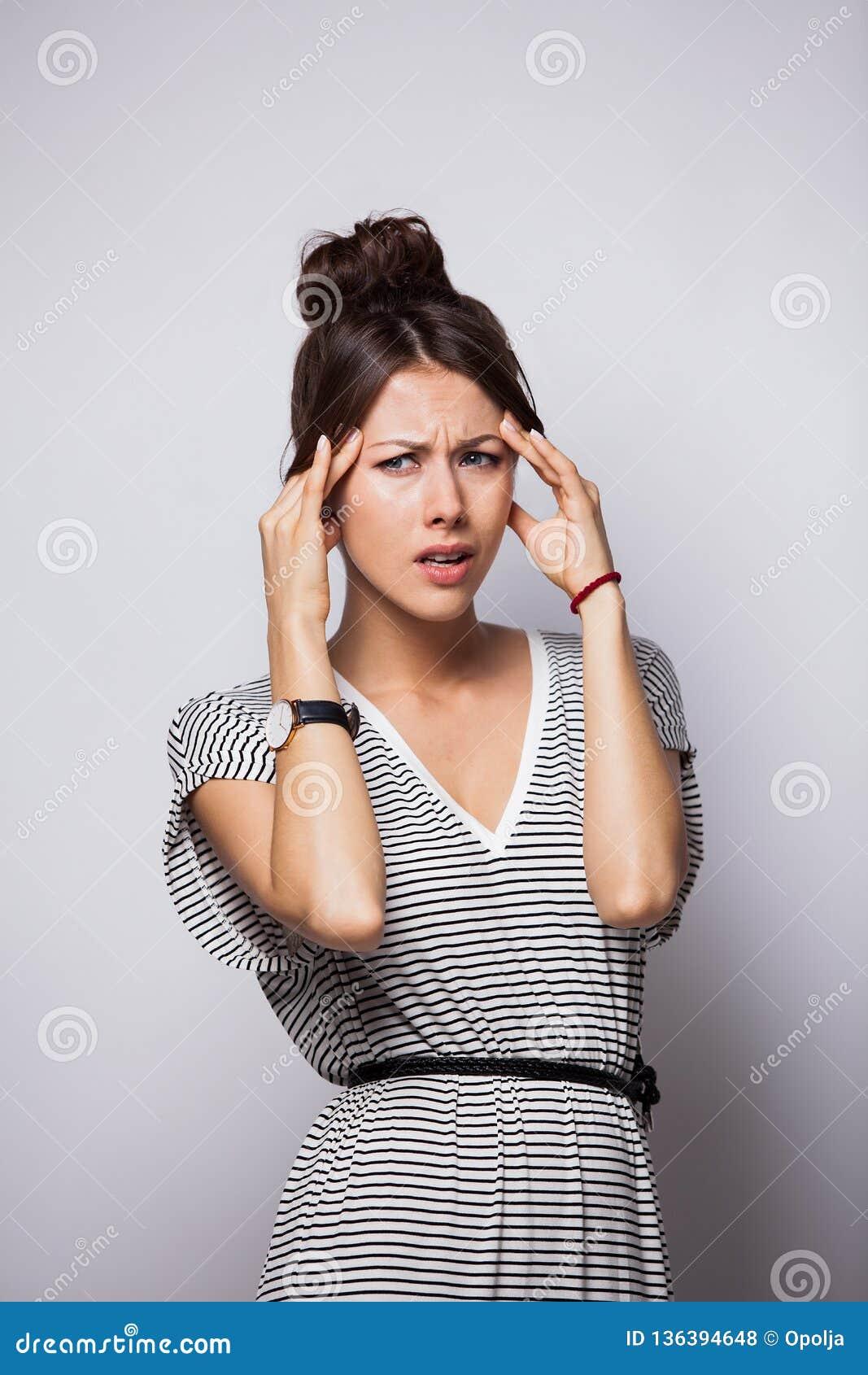 Denken, vermoeid of ziek met hoofdpijn jonge die vrouw, over witte achtergrond wordt geïsoleerd