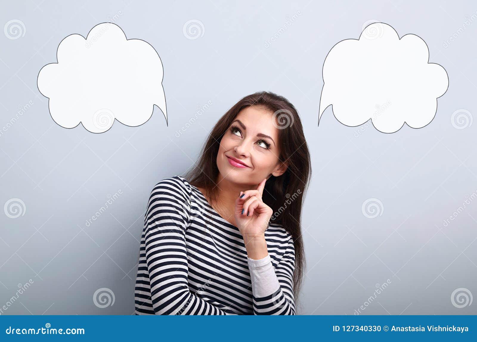 Denkende glimlachende jonge vrouw die omhoog op lege keus twee kijken bubb
