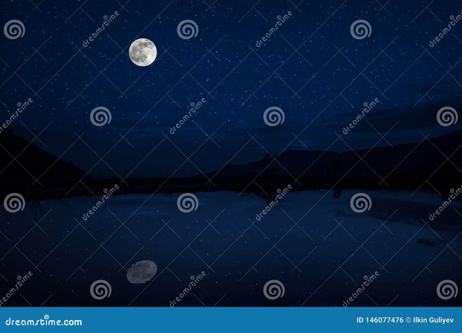 Denna dramatiska månelöneförhöjning i en djupblå nattetidhimmel betonas av markerade moln och härlig lugna sjöreflexion