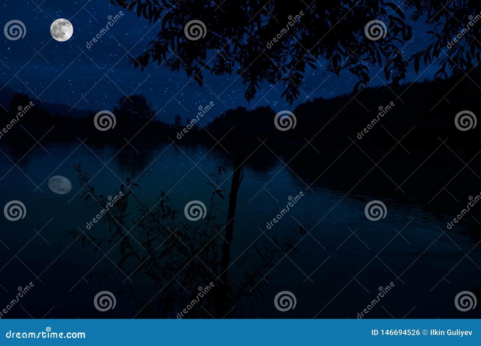 Denna dramatiska m?nel?nef?rh?jning i en djupbl? nattetidhimmel betonas av markerade moln och h?rlig lugna sj?reflexion