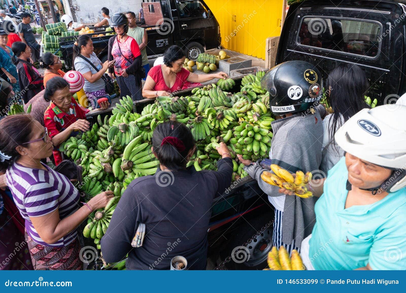 DENPASAR/BALI- 20 DE ABRIL DE 2019: el vendedor verde del plátano está vendiendo sus mercancías en un coche en una de las esquina