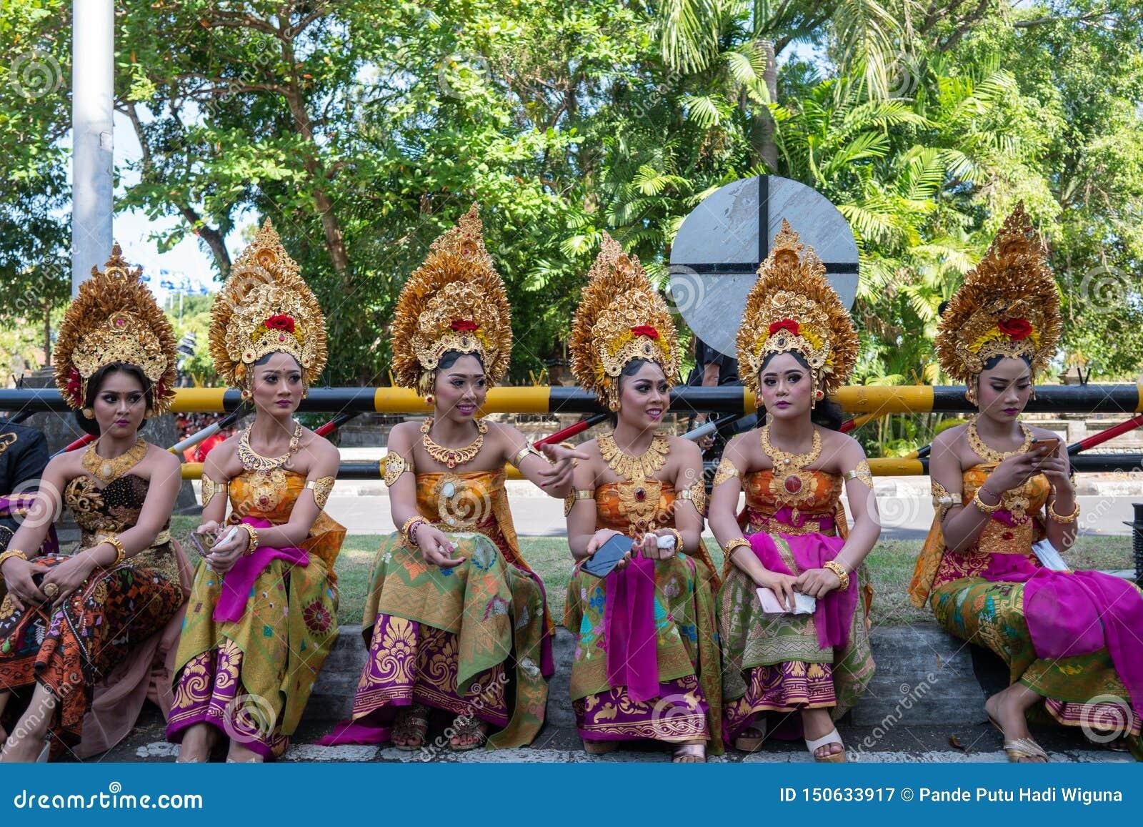 DENPASAR/BALI- 15 DE JUNHO DE 2019: Mulheres novas do Balinese que vestem a mantilha tradicional do Balinese e sarongues tradicio