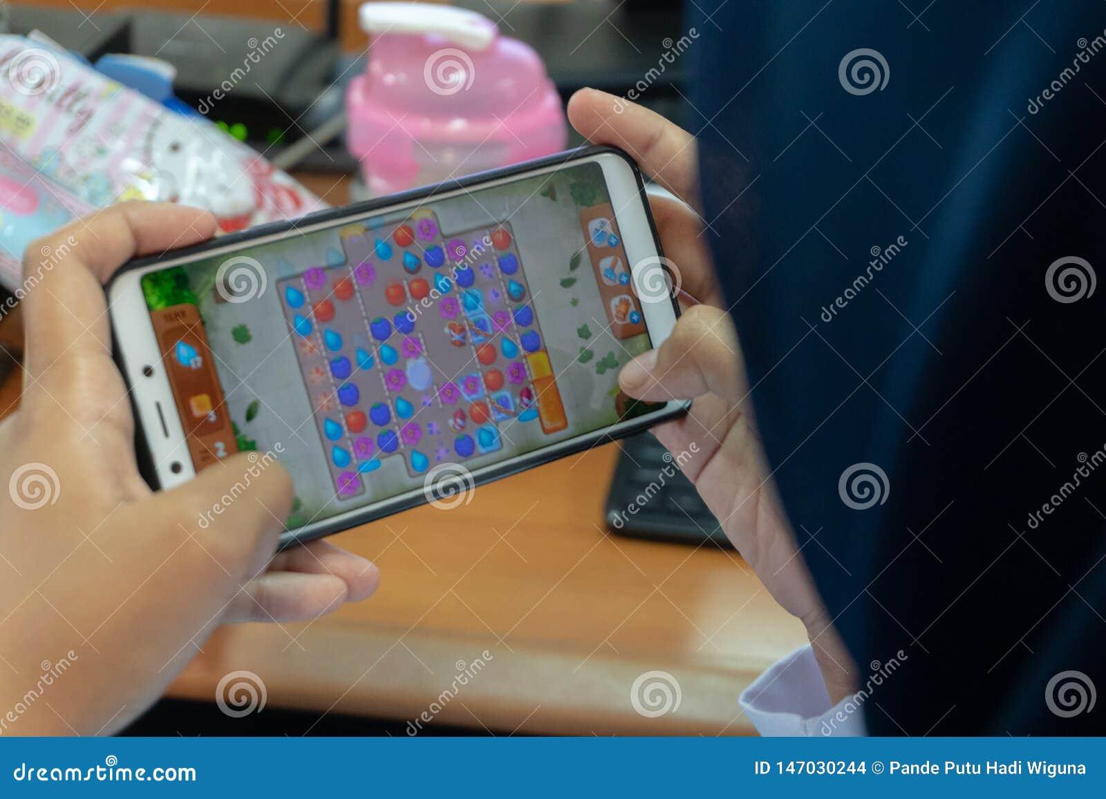 DENPASAR/BALI- 27 DE MARÇO DE 2019: uma mulher que usa um hijab está fresca jogando jogos em seu telefone celular ao esperar o mo
