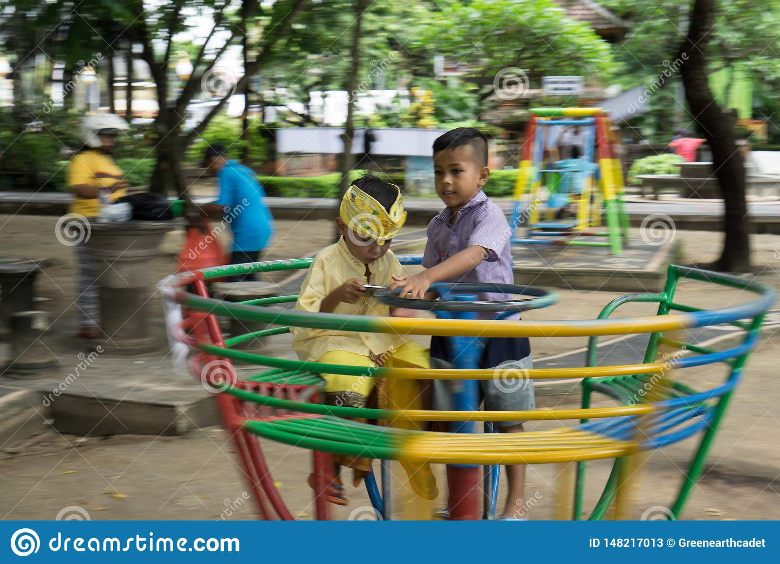 DENPASAR/BALI-DECEMBER 28 2017: dwa chłopiec bawić się na gazonie Jeden one bawić się gry z gadżetami, jak uzależniający się