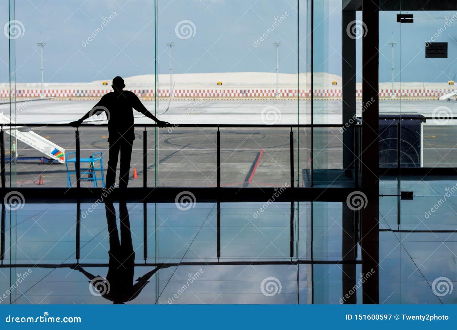 Denpasar, Bali, Indonésia: 5 de junho de 2019 - homem que olha através das janelas de vidro no aeroporto como espera seu voo