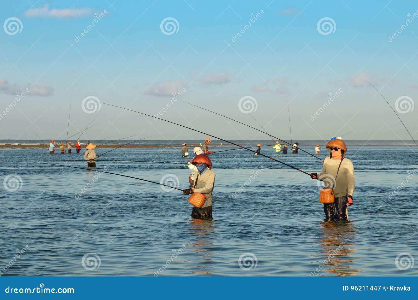 DENPASAR INDONEZJA, Maja 24 balijczyka Tradycyjni rybacy stoi w płytkiej wodzie przy niskim przypływem na plaży przy Nusa Dua, -,