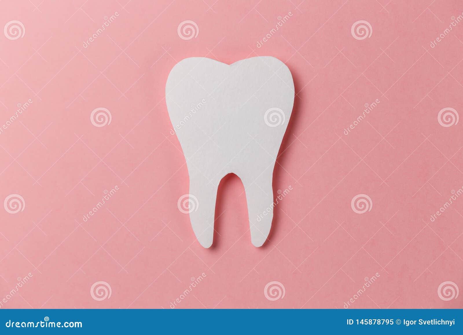 Dente branco no fundo cor-de-rosa