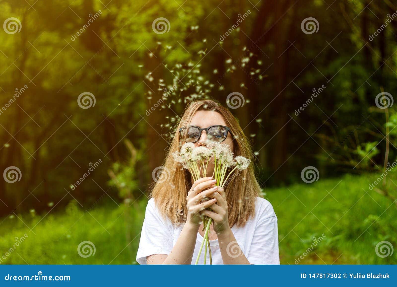 Dente di leone di salto della giovane donna nel parco di estate Bello fondo della foresta verde