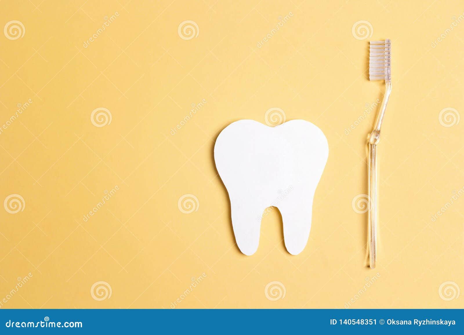 Dente do Livro Branco com a escova de dentes no fundo amarelo Conceito dental da saúde Conceito do dia do dentista