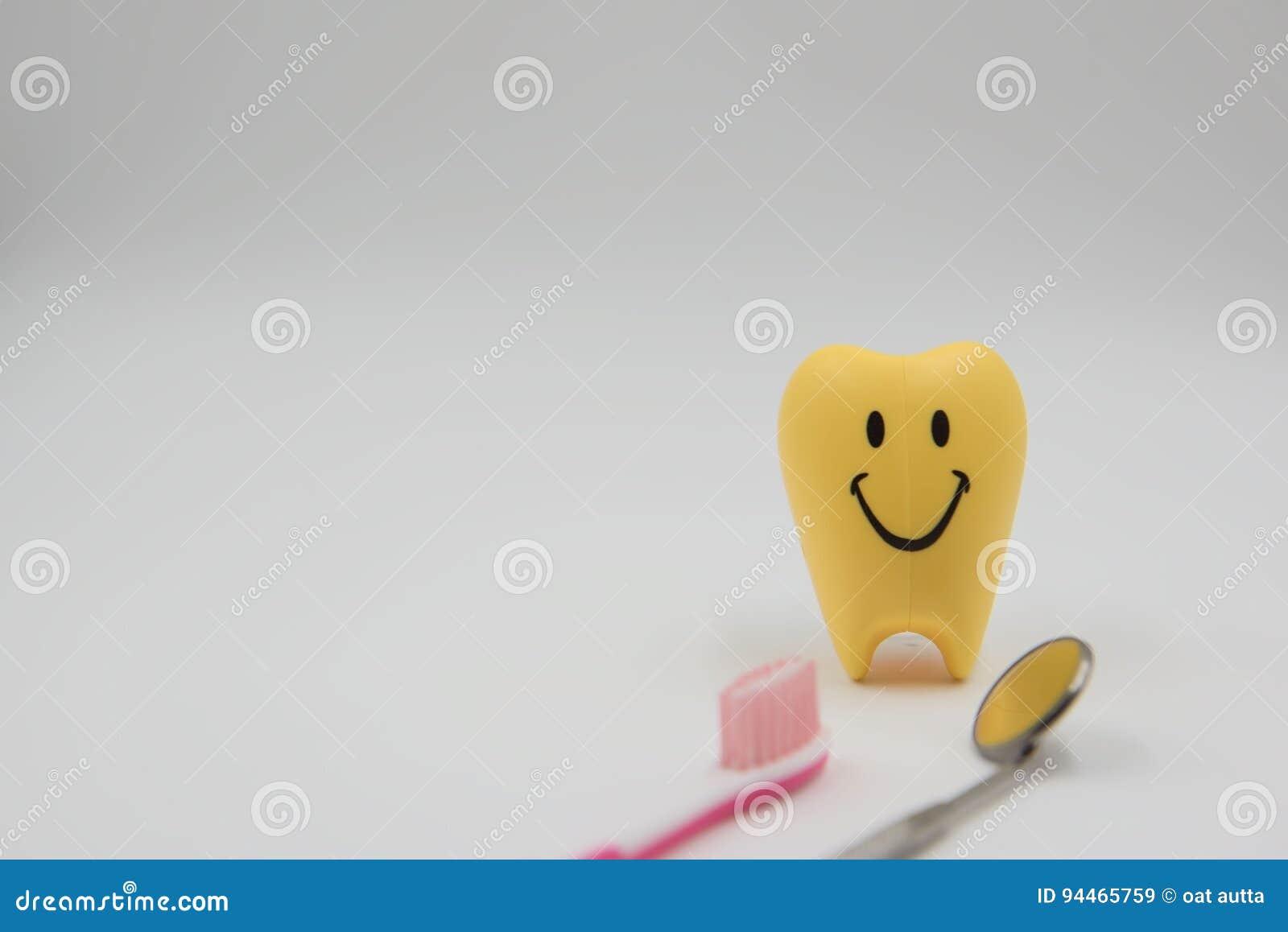 Dentes bonitos dos brinquedos do sorriso modelo amarelo na odontologia em um fundo branco