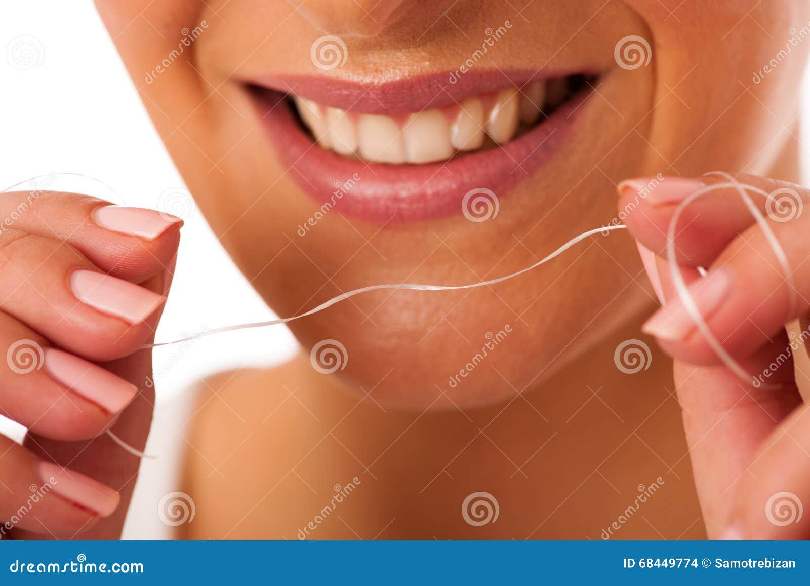 c2c83b15b Dentes da limpeza da mulher com fio dental para a higiene e h perfeitos