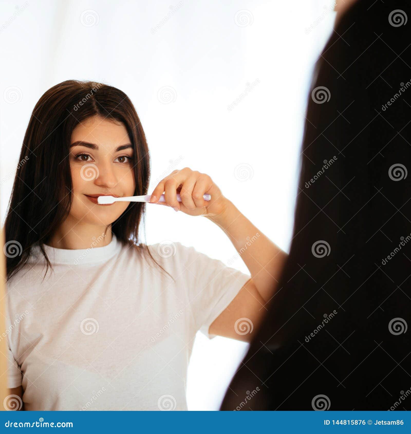 Dentes da limpeza da mulher com a escova de dentes no banheiro