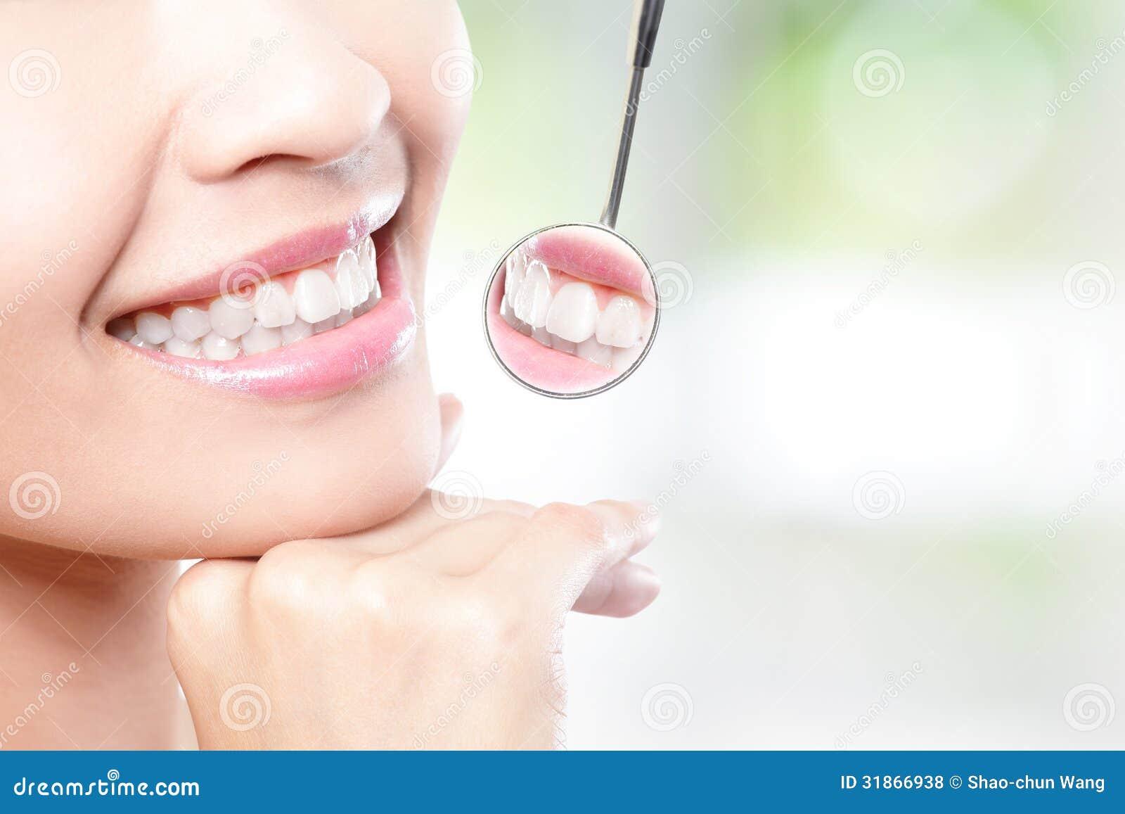 Dentes da mulher e espelho de boca saudáveis do dentista