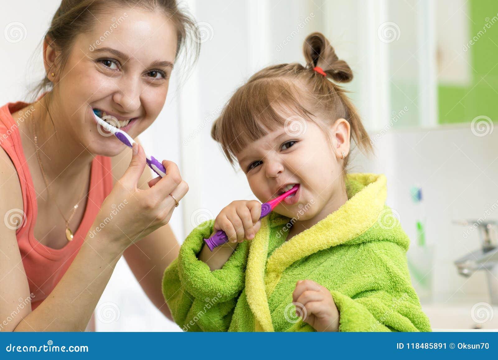 Dentes de escovadela da filha da mamã e da criança no banheiro