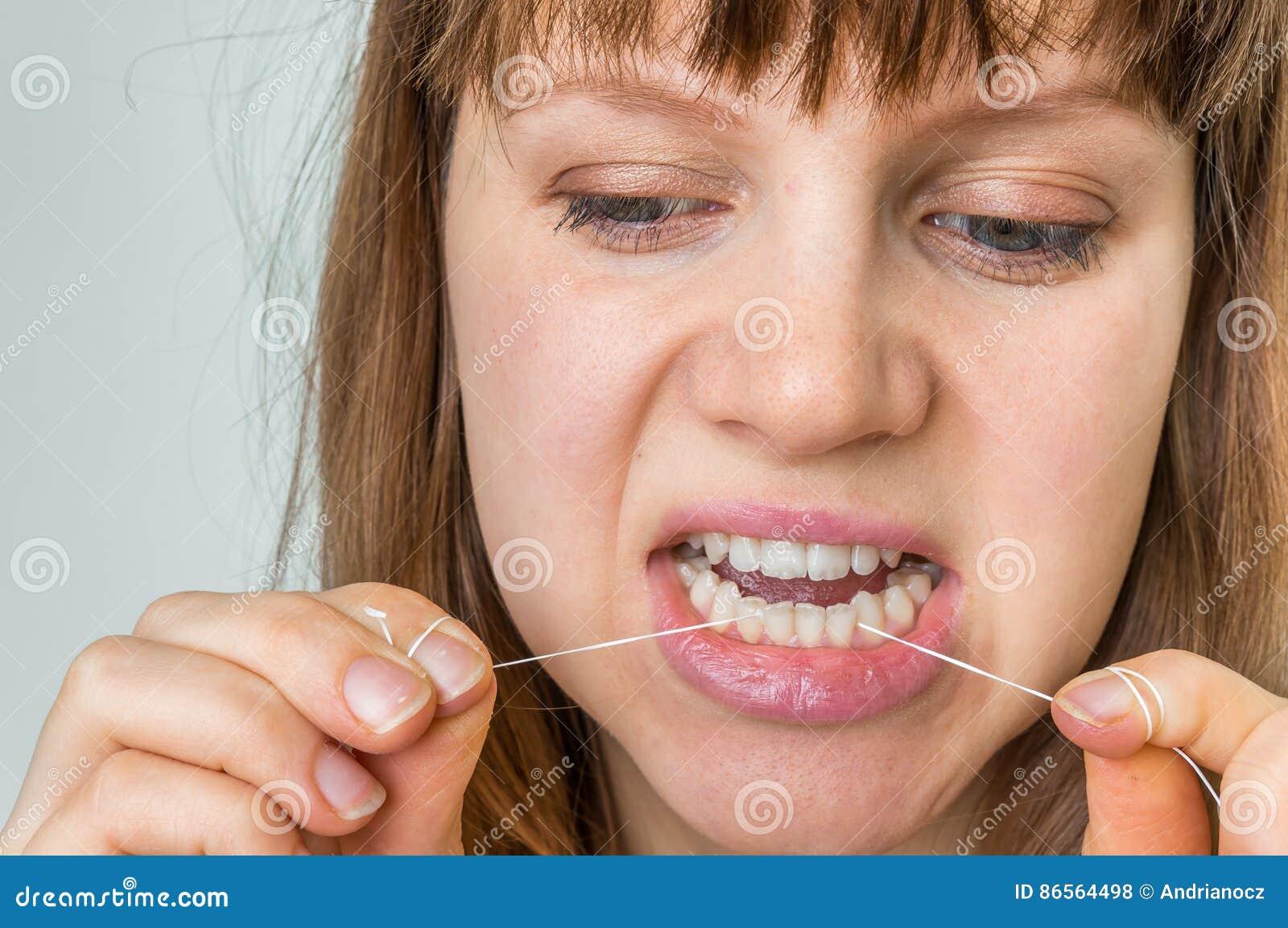 32a246795 Dentes flossing da mulher com o fio dental - oral e a higiene dos dentes
