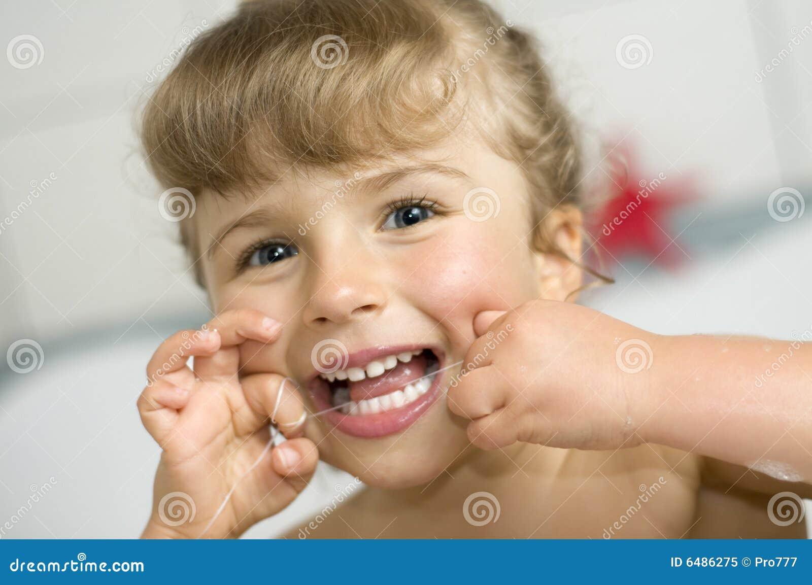 Denti di pulizia della ragazza da filo per i denti