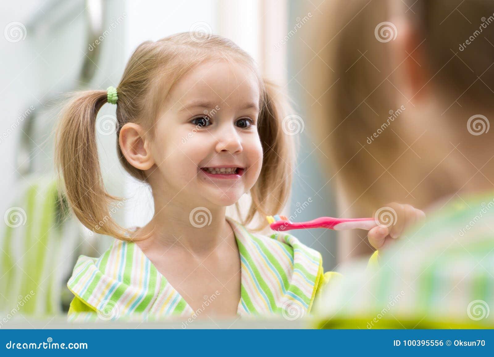 Denti di spazzolatura della ragazza sveglia del bambino e guardare in specchio in bagno