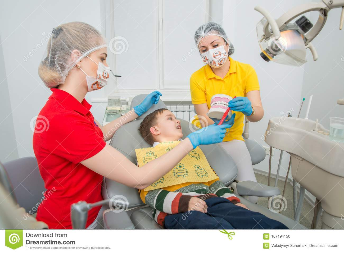 The dentist with assistent showing the little boy how to clean the teeth with a toothbrush on an artificial jaw dummy