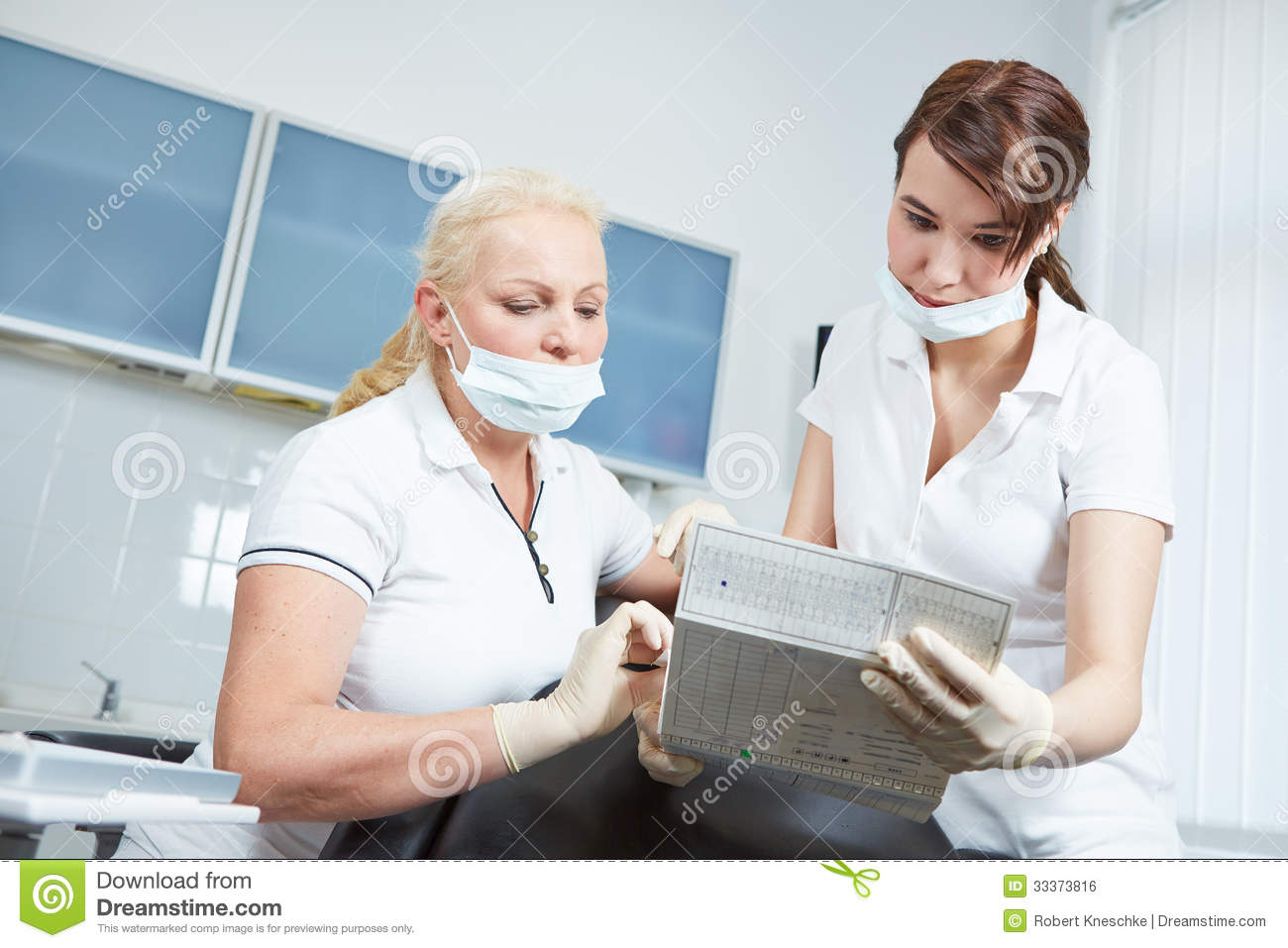 Dentist And Dental Assistant Reading Medical Recor Royalty