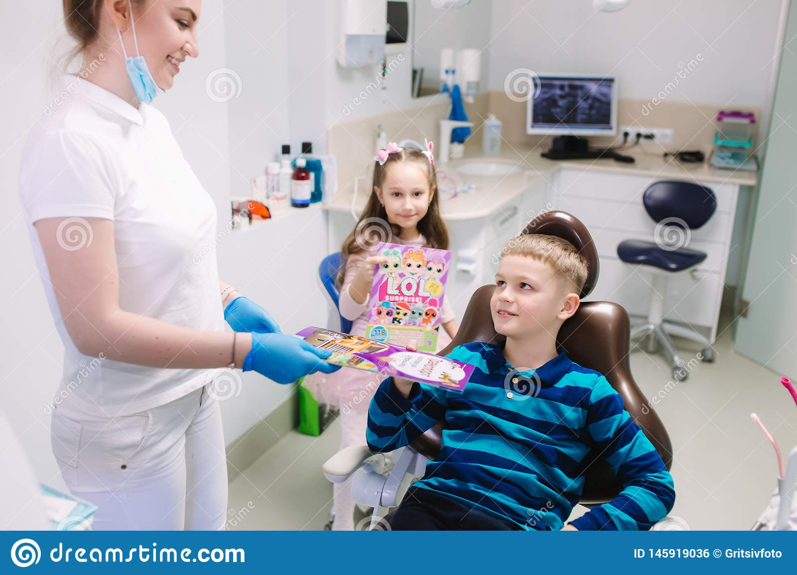 Dentist give a toy for little patient, happy children get a present