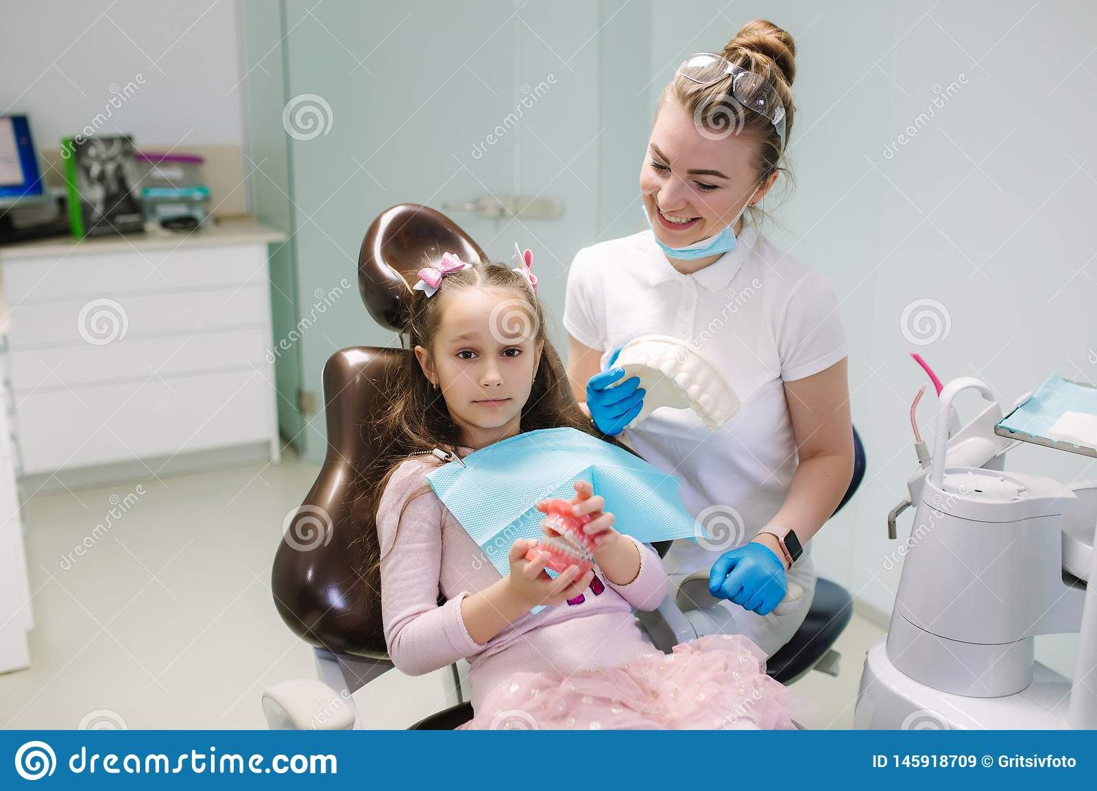 Dentist show to little girl how to wash teeth