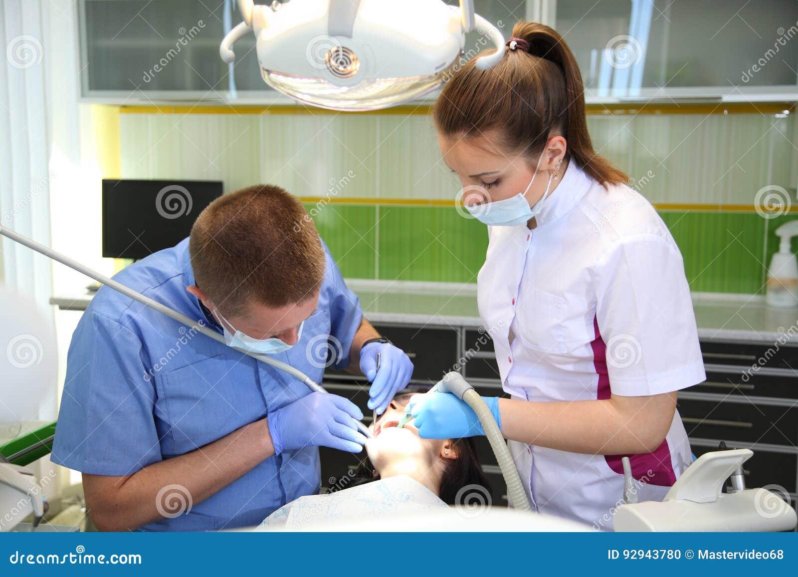 Dentista che tratta i denti del ` una s del paziente con gli strumenti dentari in clinica dentaria odontoiatria