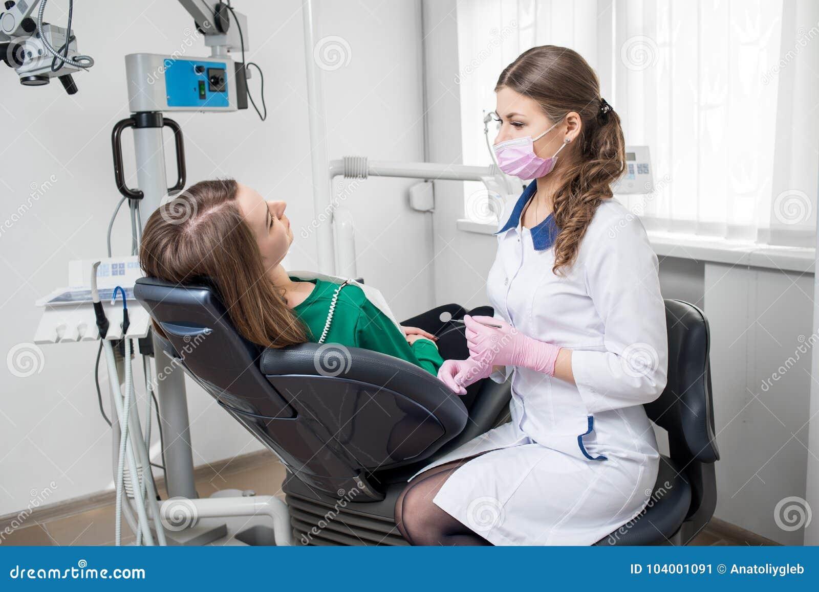 Dentista de sexo femenino joven con el paciente hermoso de la mujer antes del procedimiento dental en oficina dental moderna odon