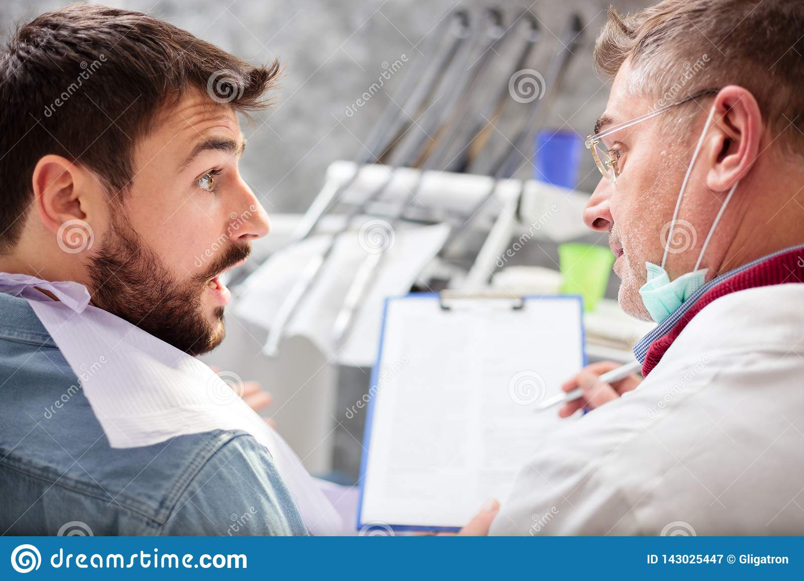 Dentista de sexo masculino maduro que escribe a los detalles del paciente sobre un tablero, consultando durante el examen en clín