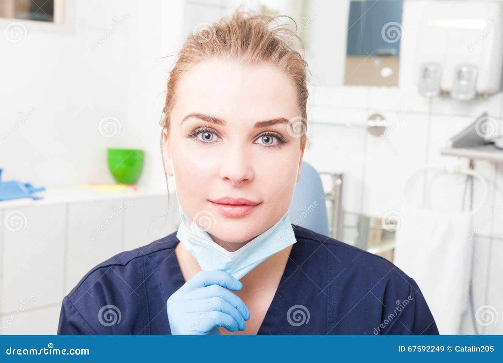 Dentista de sorriso da mulher no close-up que guarda a máscara dental