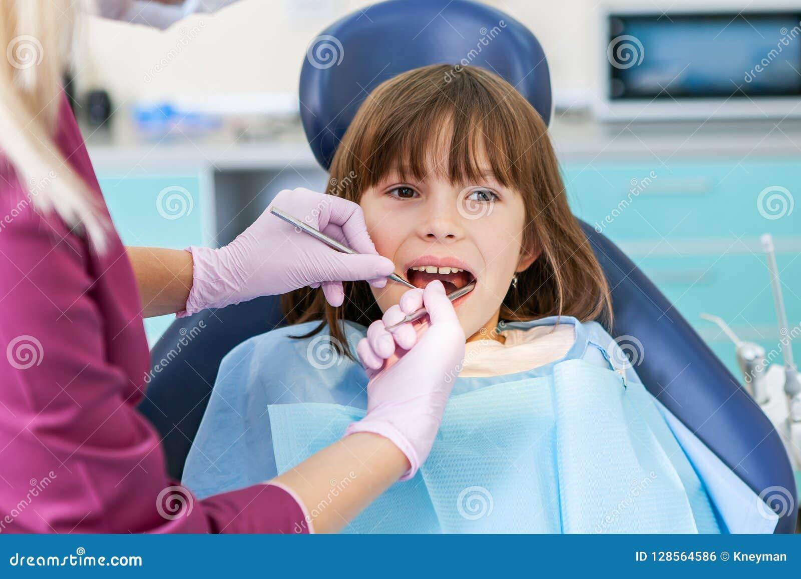 Dentista fêmea no escritório dental que fala com paciente fêmea e que prepara-se para o tratamento Caçoa o stomatology