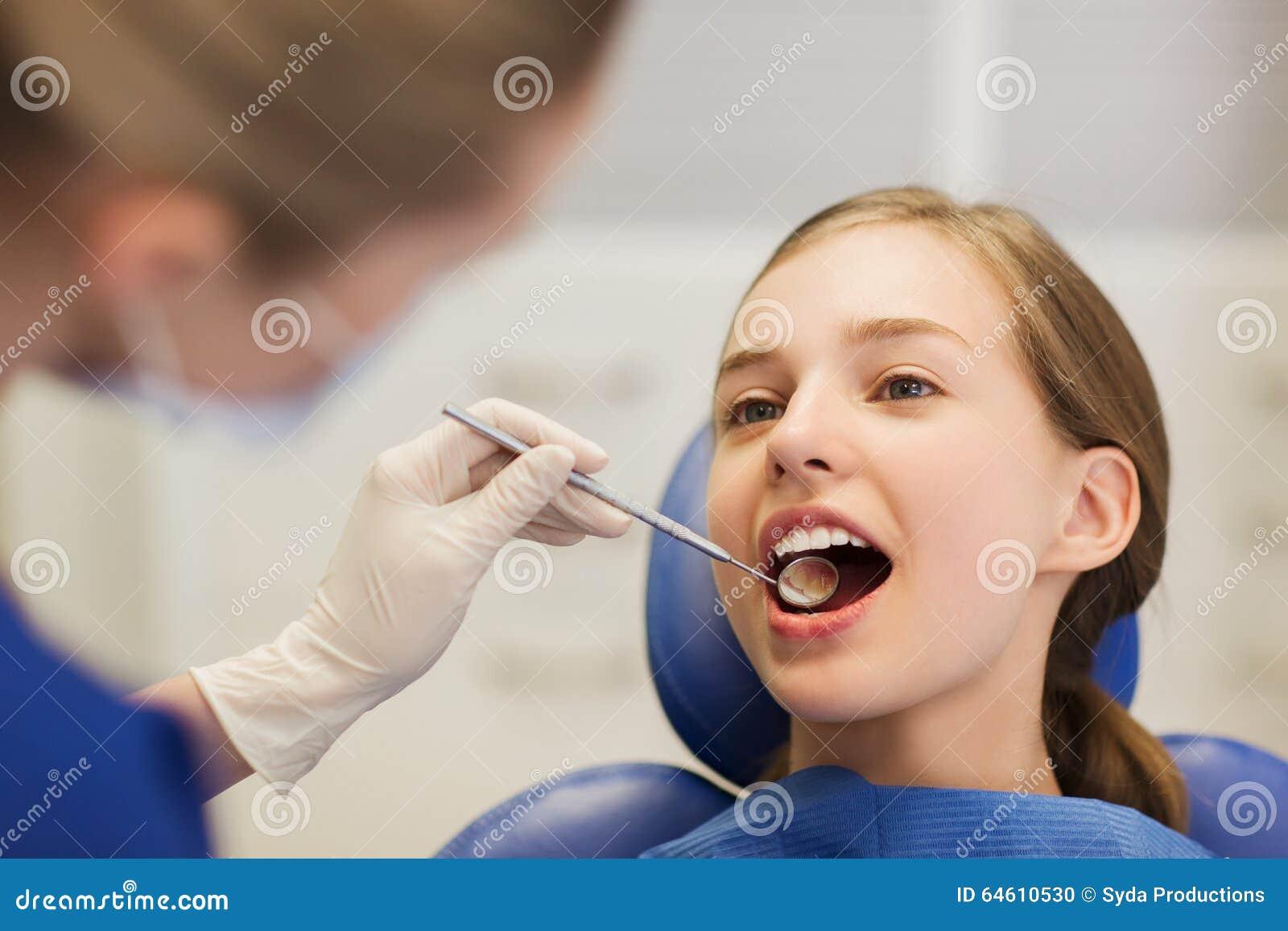 Dentista fêmea que verifica os dentes pacientes da menina