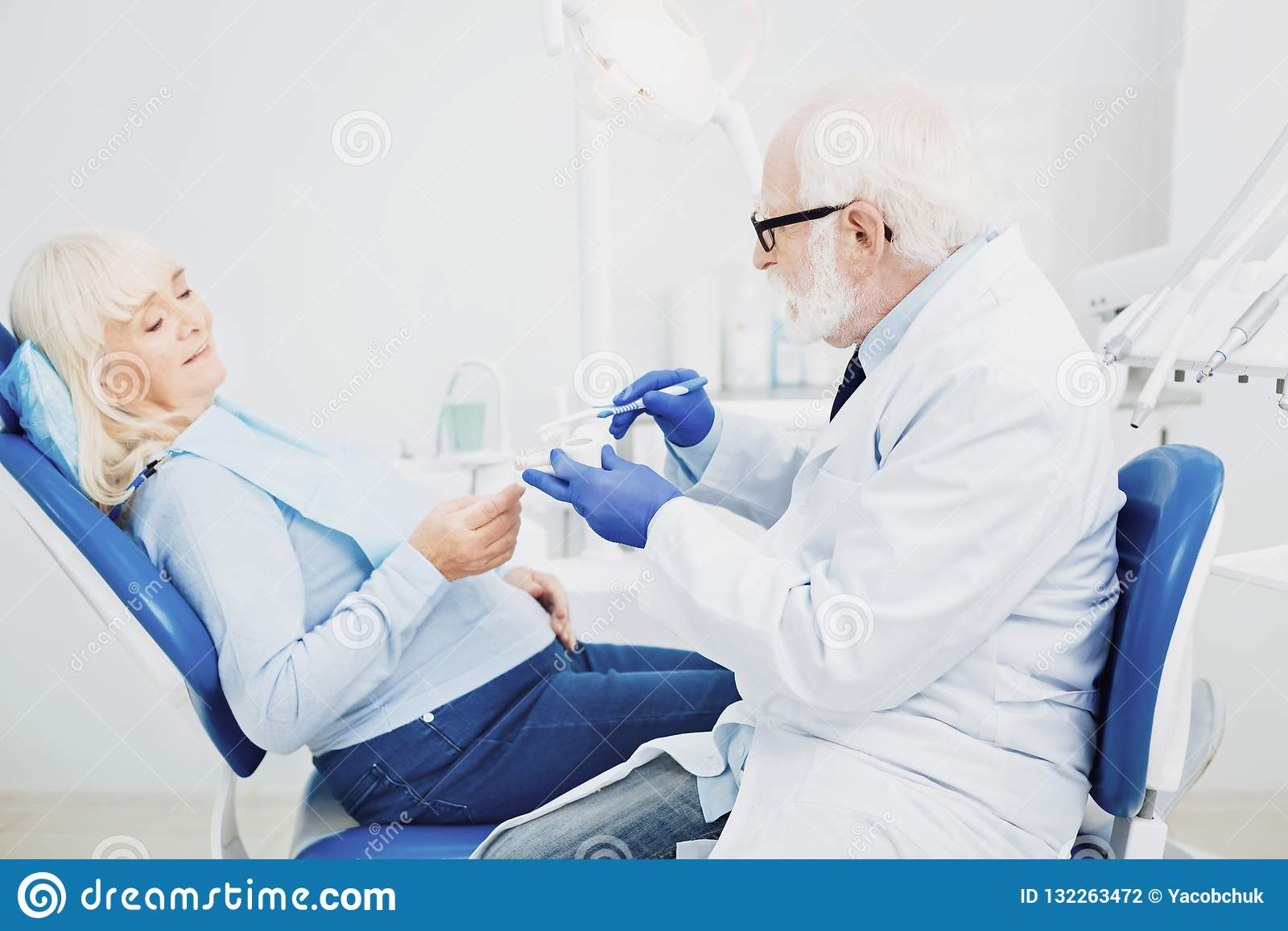 Dentista maschio messo a fuoco che consiglia paziente