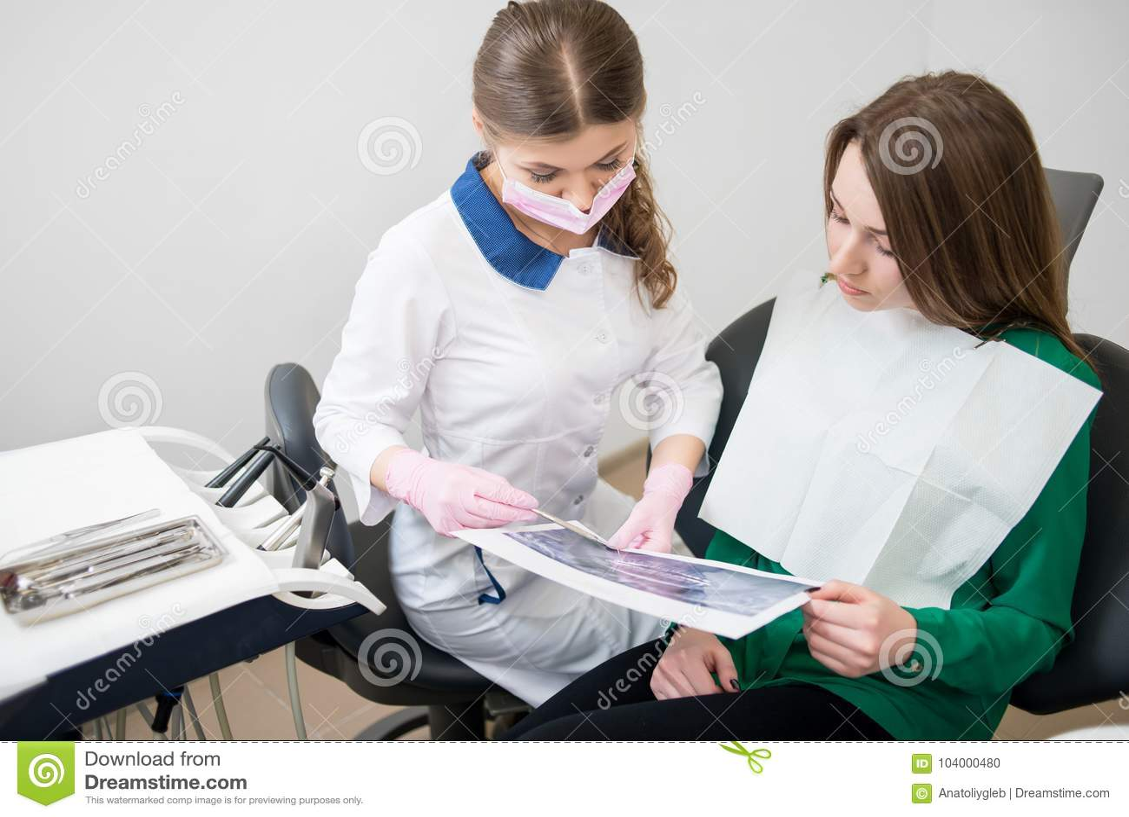 Dentista que fala com o paciente fêmea na clínica dental e que prepara-se para o tratamento Imagem de exame do raio X dentistry