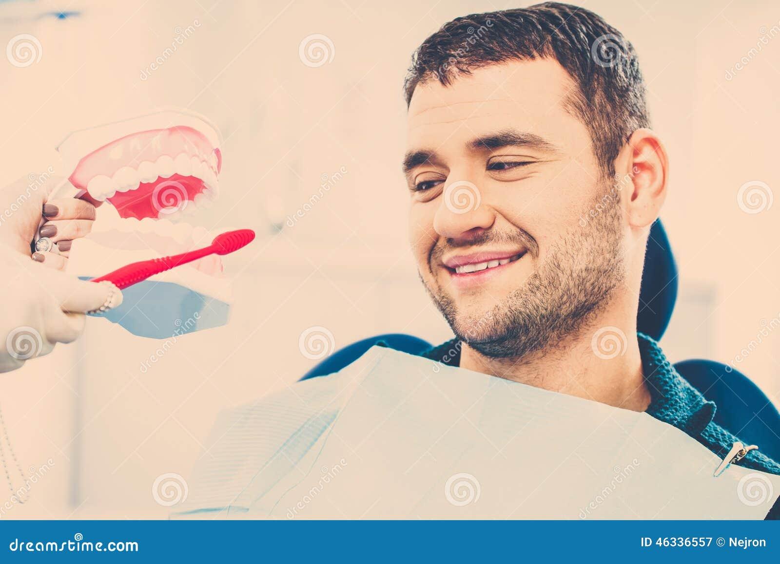 Dentista que muestra al paciente del hombre cómo limpiar los dientes