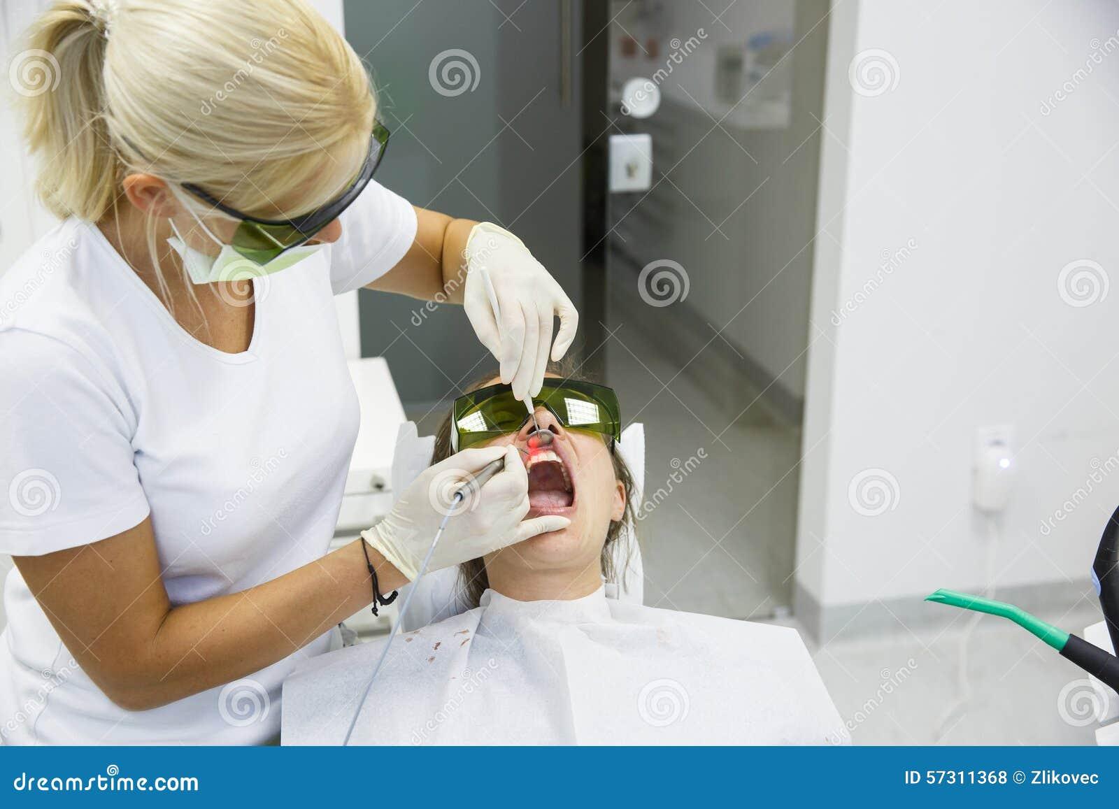 Dentista que usa um laser dental do diodo moderno
