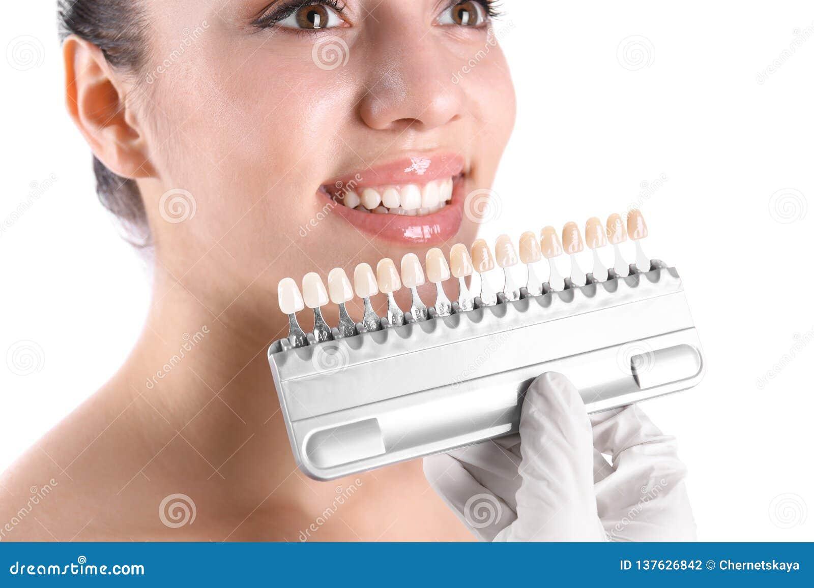 Dentista que verifica a cor dos dentes da jovem mulher no fundo branco