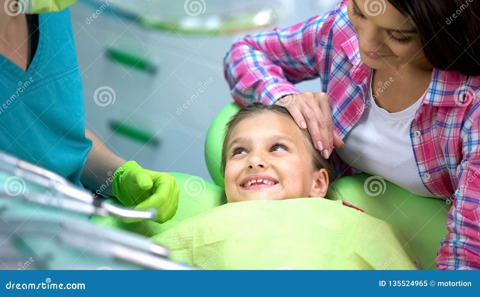 Dentista que visita sonriente de la muchacha preescolar, ningún miedo después del procedimiento, odontología de los niños