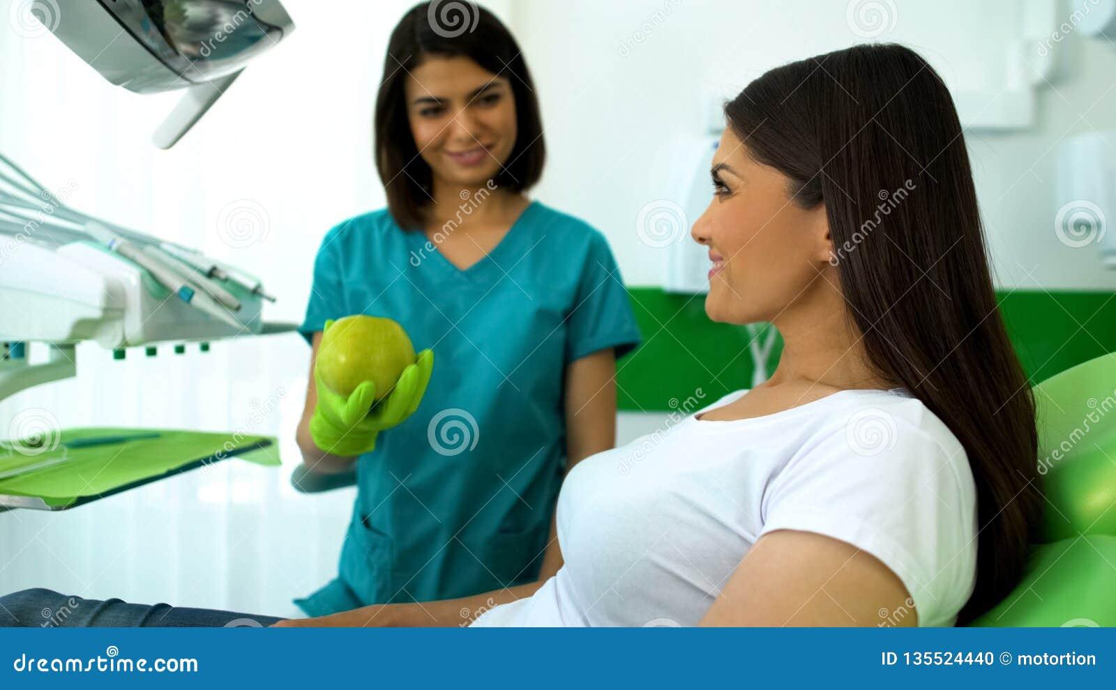 Dentista sorridente di signora che dà mela verde al paziente, raccomandazioni di sanità