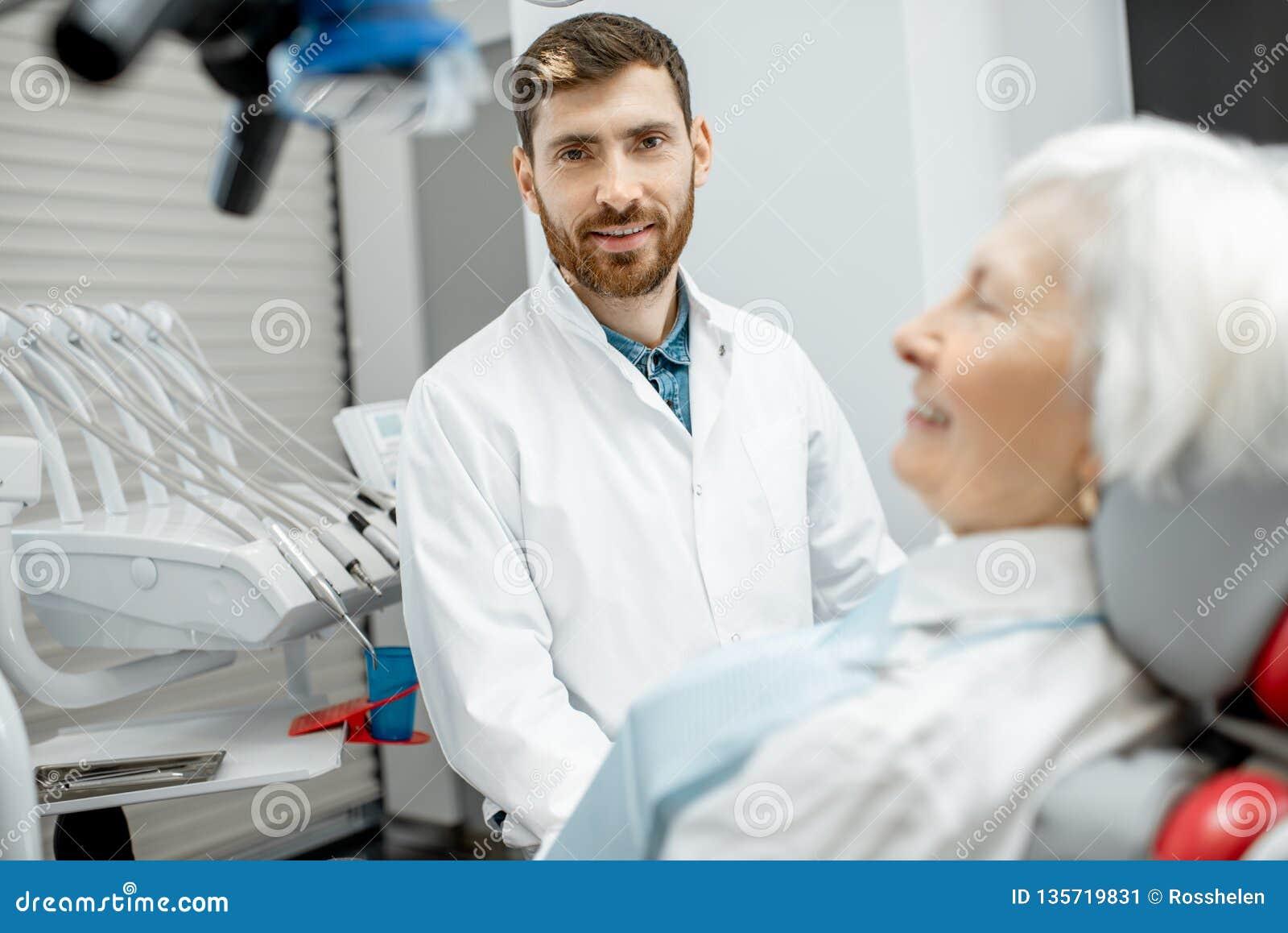 Dentiste avec la patiente supérieure de femme dans le bureau dentaire