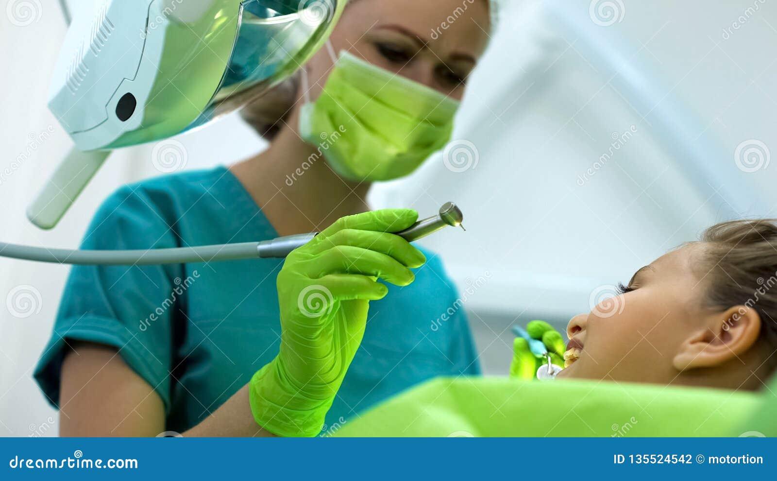 Dentiste disposant à forer la dent malade, procédure de attente d adolescente courageuse