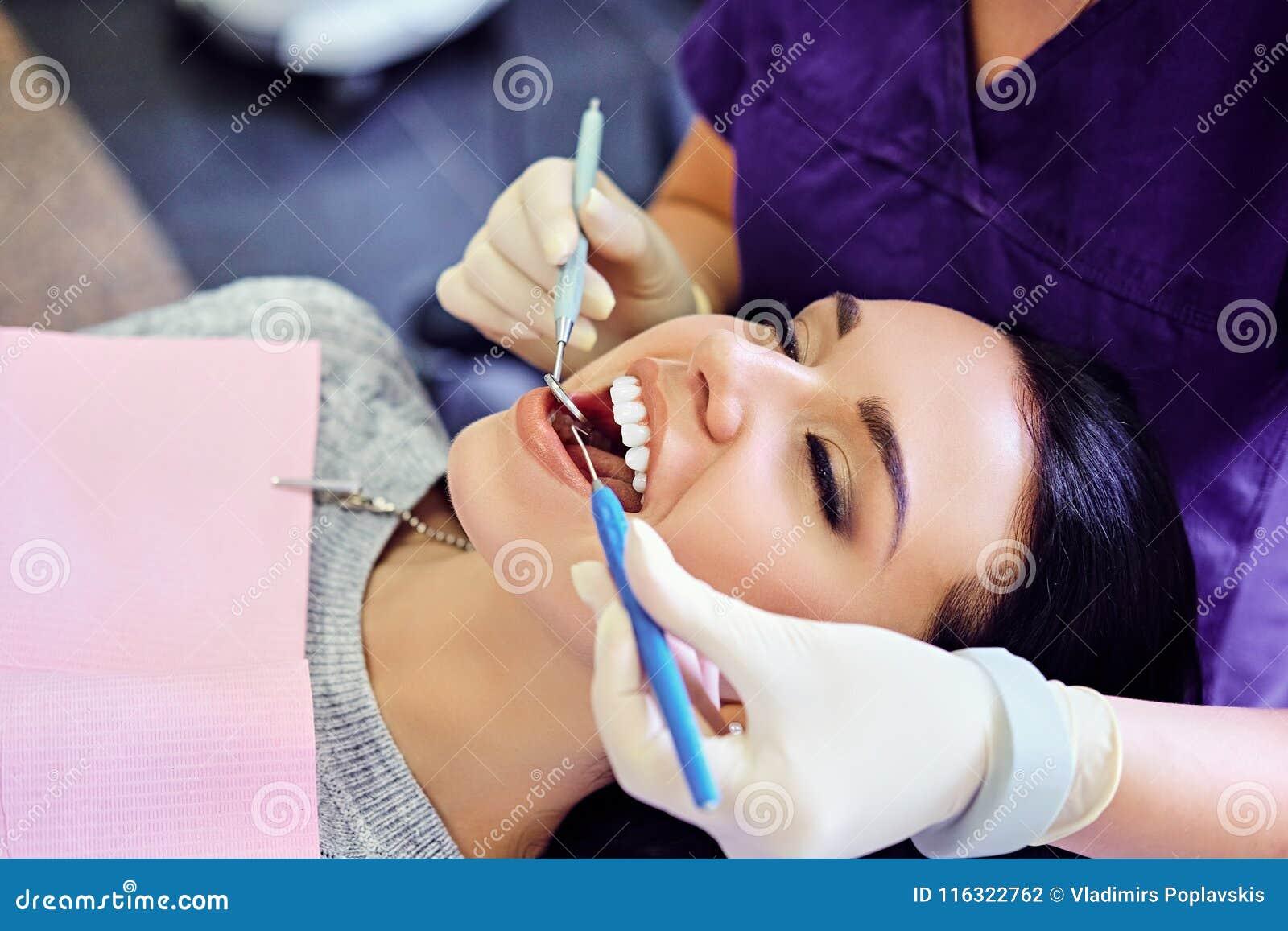 Dentiste examinant les dents femelles du ` s en art dentaire