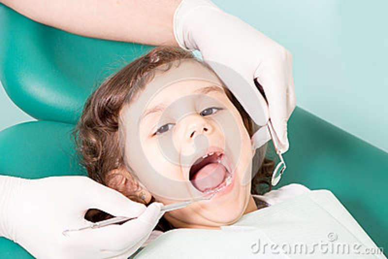Dentiste examinant peu de girl& x27 ; dents de s