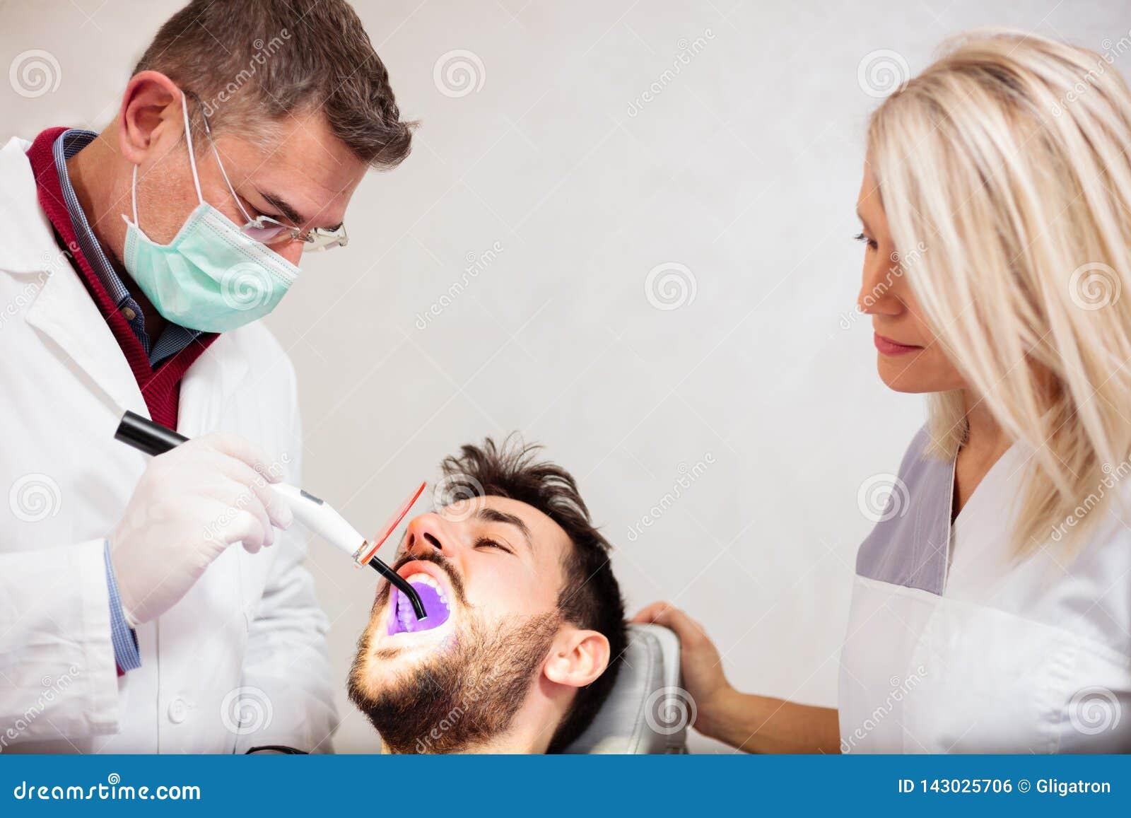 Dentiste masculin mûr et beau jeune assistant féminin employant la lumière UV, blanchissant des dents d un jeune patient masculin