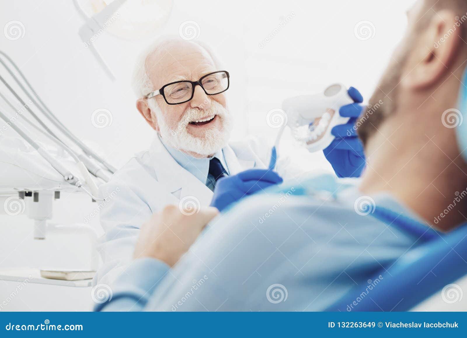 Dentiste masculin positif partageant sa connaissance