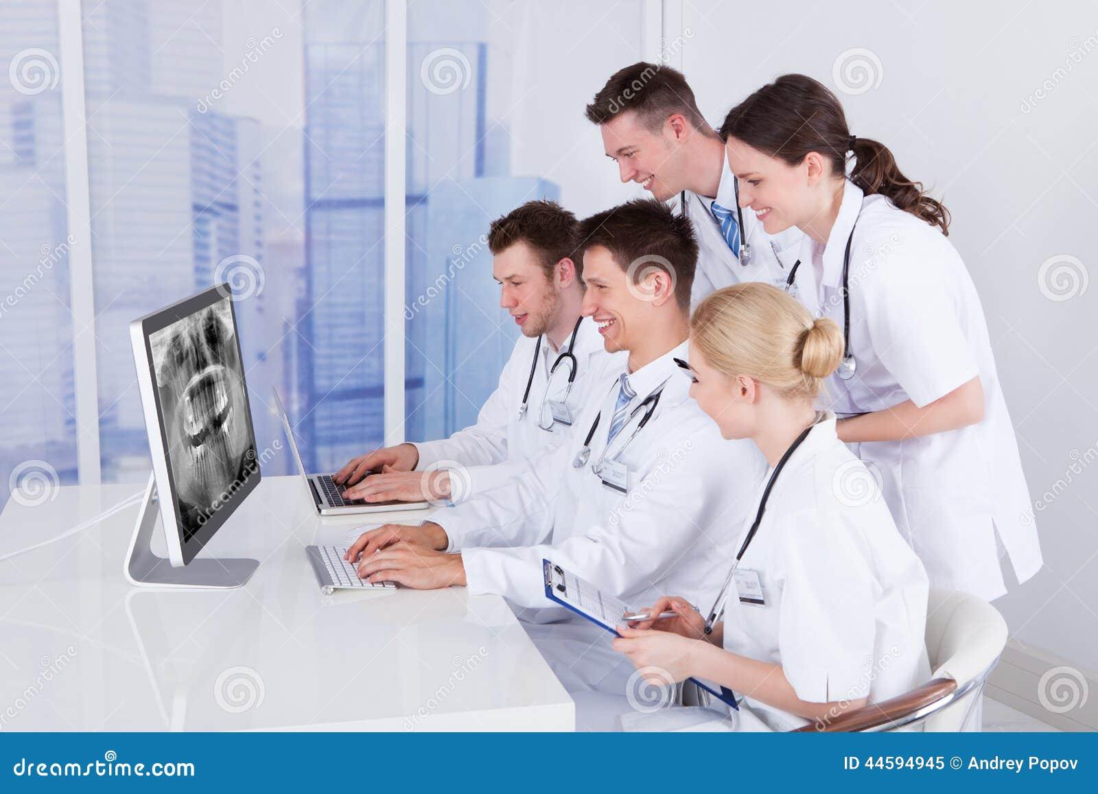 Dentistes examinant le rayon X de mâchoire sur l ordinateur