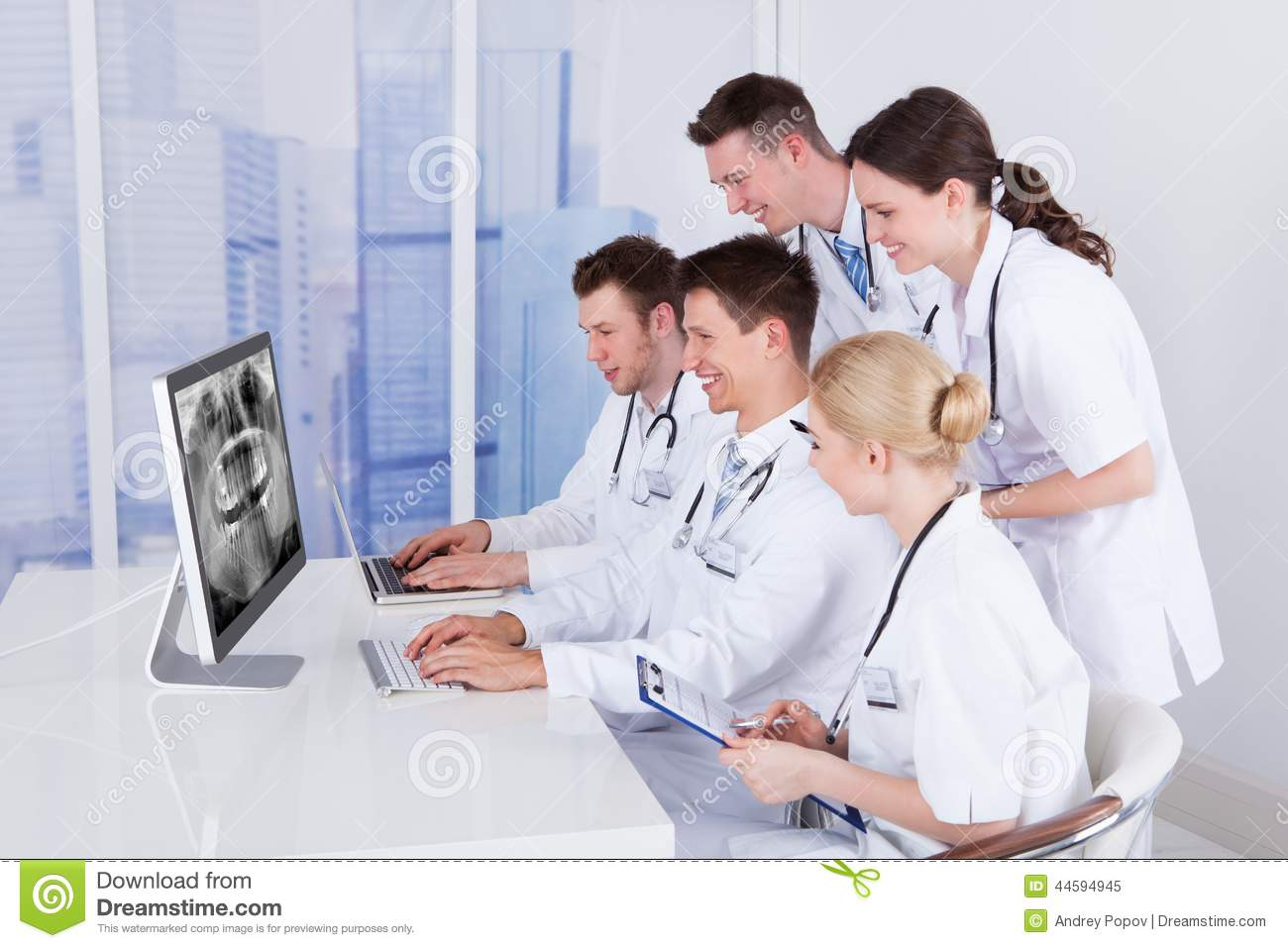 Dentists examining jaw xray on computer