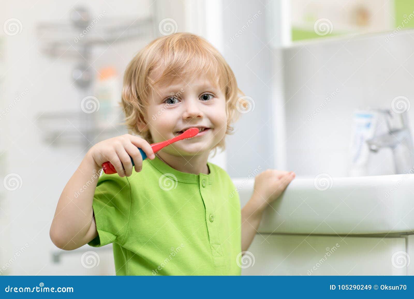 Dents de brossage heureuses d enfant ou d enfant dans la salle de bains Hygiène dentaire