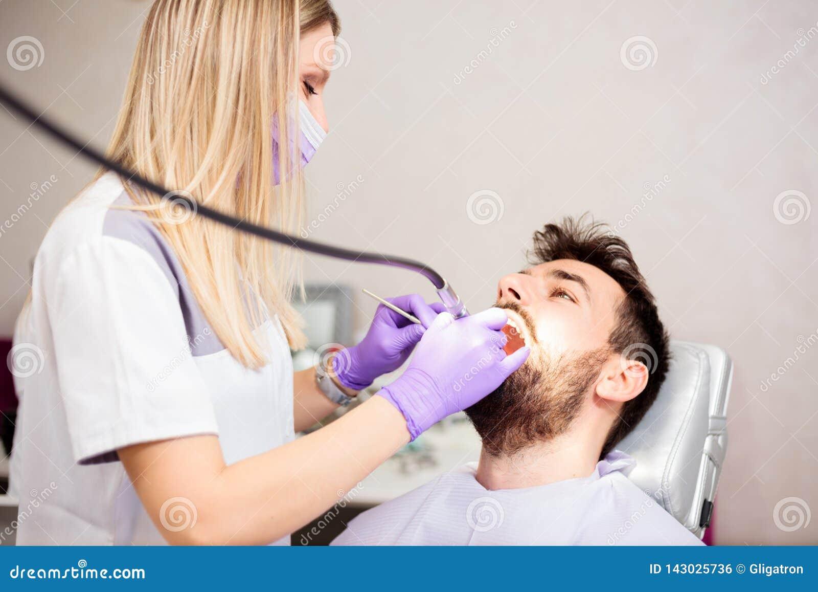 Dents de polissage de beau jeune dentiste féminin d un jeune patient masculin dans la clinique dentaire
