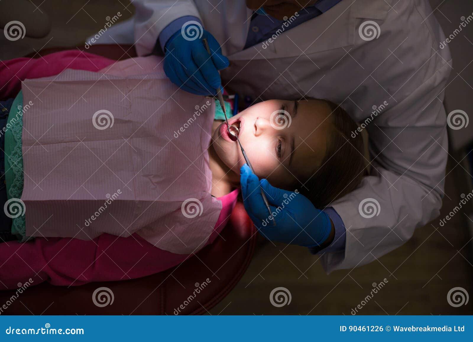 Dentysta egzamininuje młodego pacjenta z narzędziami